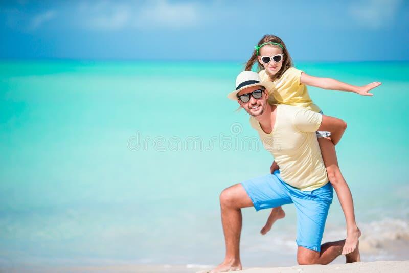Padre felice ed il suo bambino adorabile alla spiaggia tropicale divertendosi insieme fotografie stock