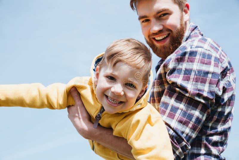 Padre felice ed il suo piccolo figlio divertendosi insieme immagini stock