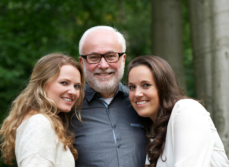 Padre feliz así como dos hijas sonrientes imagen de archivo libre de regalías