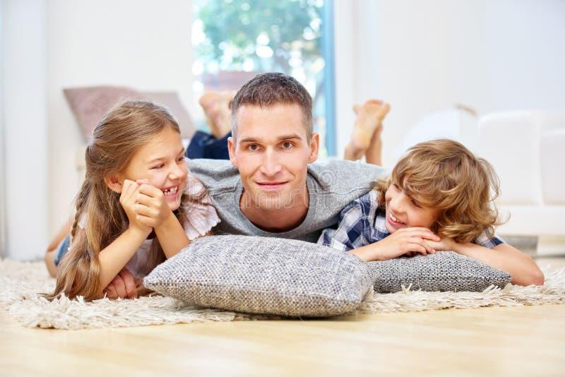 Padre feliz con dos niños en casa imagen de archivo libre de regalías