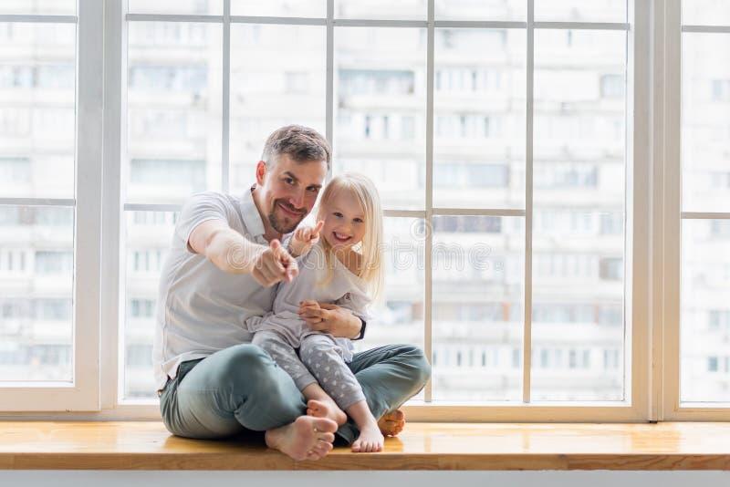 Padre feliz con hija apuntando con los dedos contra la ventana imagen de archivo libre de regalías