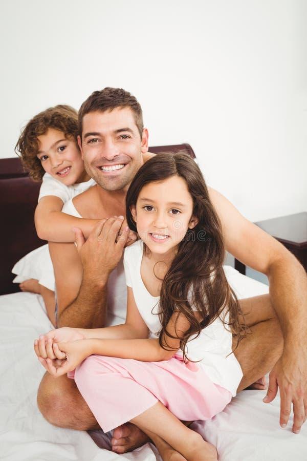 Padre feliz con la hija y el hijo en cama en casa imagen de archivo