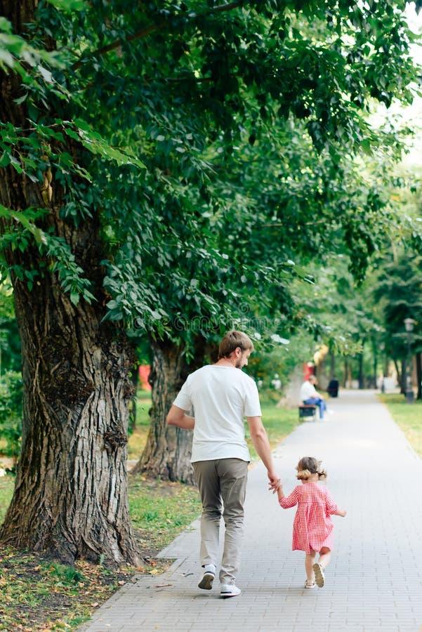 Padre feliz con la pequeña hija en el parque, verano al aire libre fotografía de archivo libre de regalías
