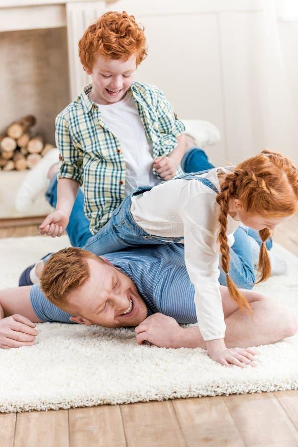 Padre feliz con los niños adorables del pelirrojo que juegan y que se divierten junto en piso imagenes de archivo