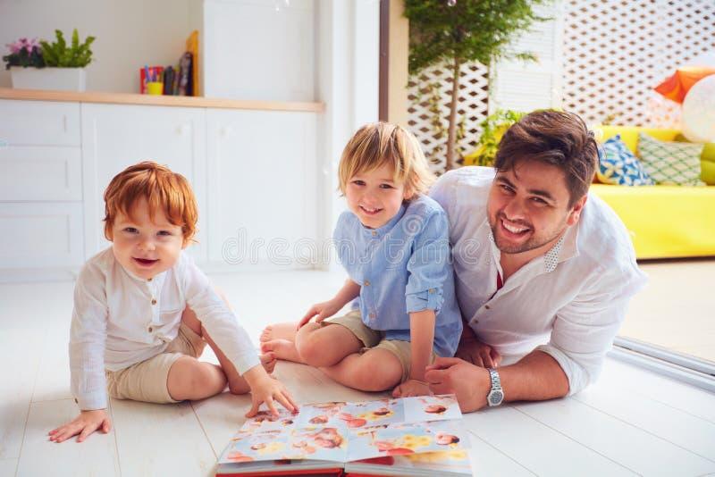 Padre feliz con los niños, hijos que se divierten en casa imagen de archivo