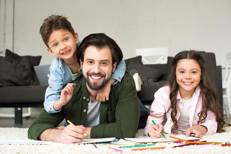 padre feliz con los niños lindos que sonríen en la cámara mientras que dibuja con los lápices coloreados imágenes de archivo libres de regalías