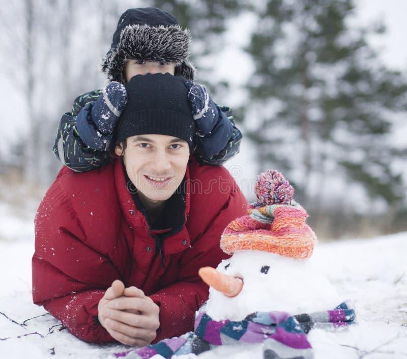 Padre feliz con su hijo afuera con el muñeco de nieve fotografía de archivo