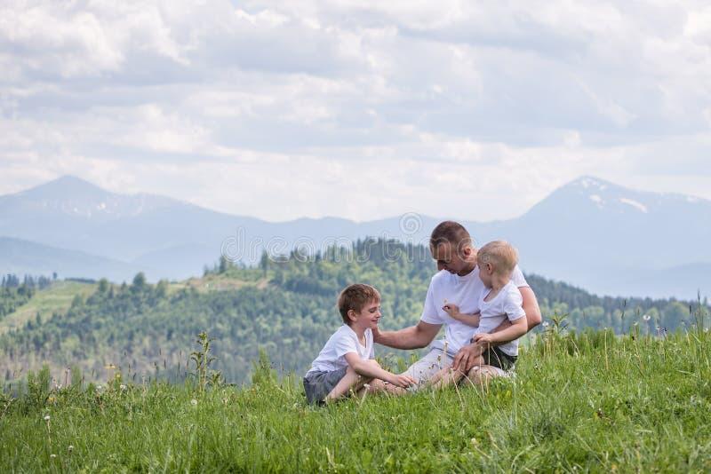 Padre feliz con sus dos hijos jovenes que se sientan en la hierba en un fondo del bosque, de montañas y del cielo verdes con las  fotografía de archivo