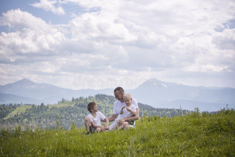 Padre feliz con sus dos hijos jovenes que se sientan en la hierba en un fondo del bosque, de montañas y del cielo verdes con las  foto de archivo libre de regalías