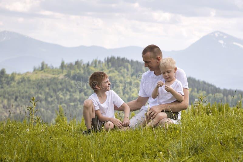 Padre feliz con sus dos hijos jovenes que se sientan en la hierba en un fondo del bosque, de montañas y del cielo verdes con las  imágenes de archivo libres de regalías
