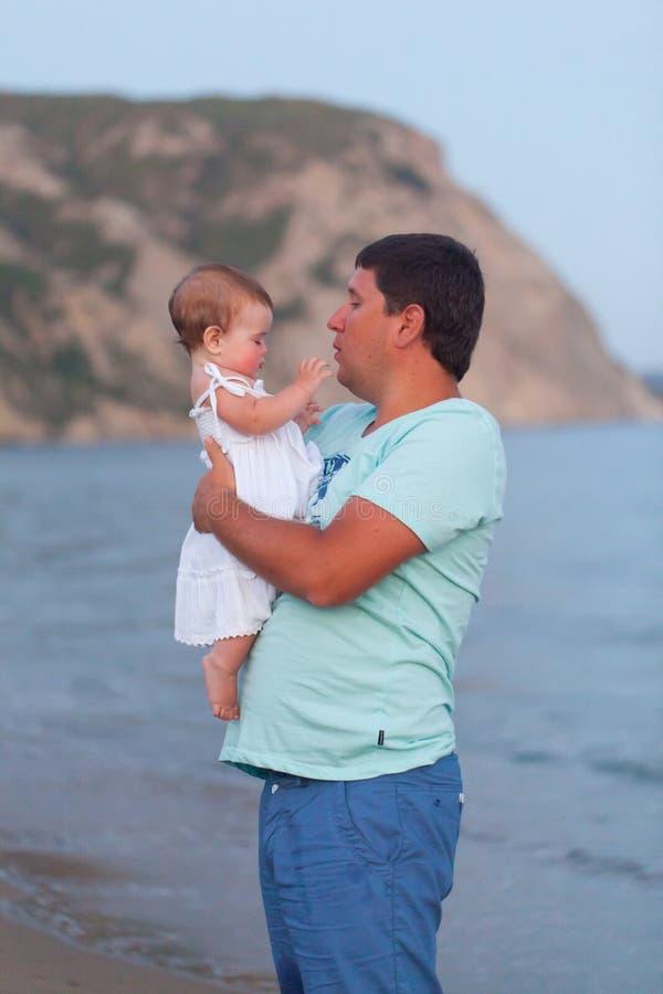 Padre feliz con una pequeña hija en una playa fotos de archivo libres de regalías
