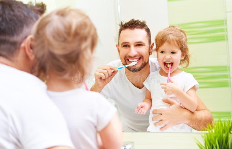 Padre feliz de la familia y muchacha del niño que cepilla sus dientes en bathroo imagen de archivo libre de regalías