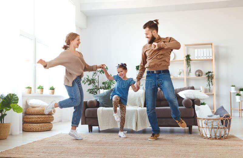 Padre feliz de la madre de la familia e hija del niño que baila en casa fotos de archivo libres de regalías