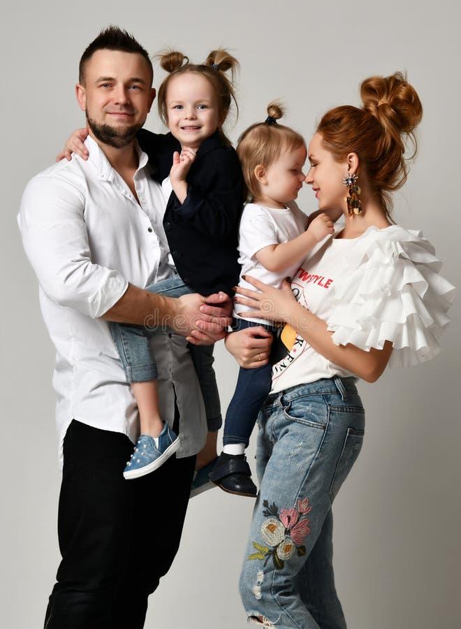 Padre feliz de la madre de la familia y dos muchachas de la hija que sonríen en estudio gris imagen de archivo