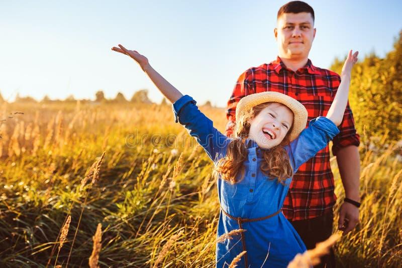 Padre feliz e hija que caminan en prado del verano, teniendo la diversión y jugar imagen de archivo