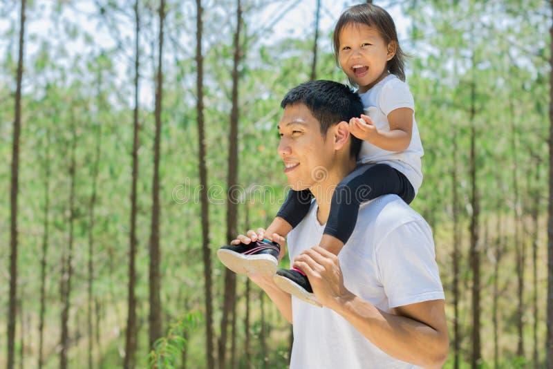 Padre feliz e hija que juegan afuera en un bosque verde imagen de archivo