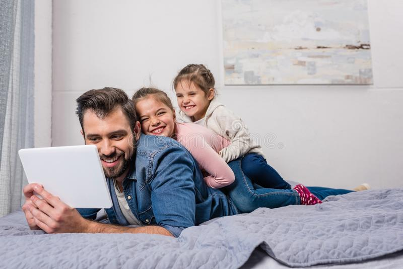 padre feliz e hijas jovenes que se relajan en cama fotos de archivo