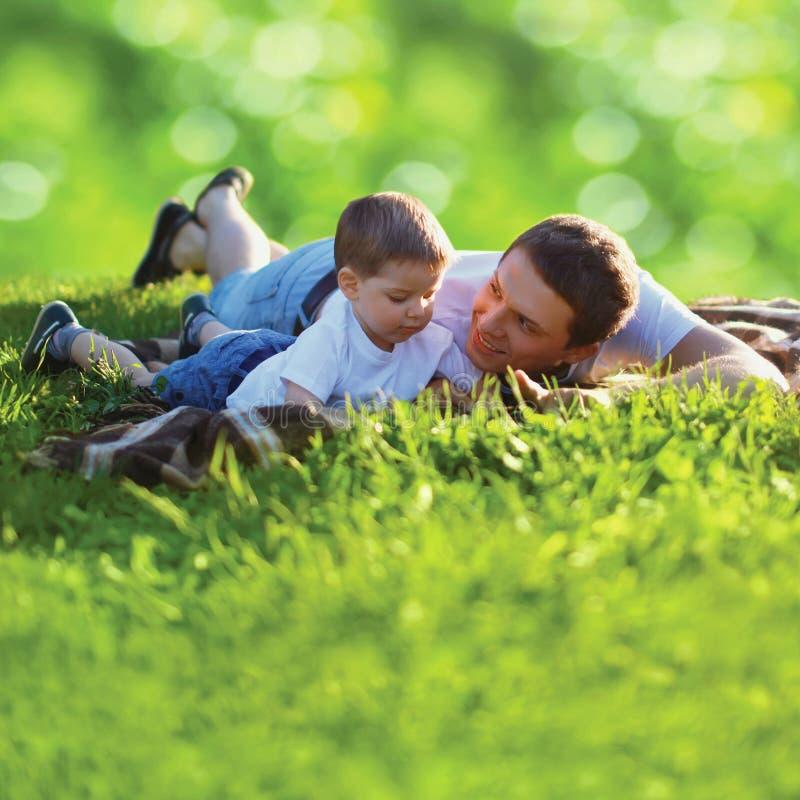 Padre feliz e hijo de la foto del verano junto que mienten en hierba fresca fotografía de archivo libre de regalías