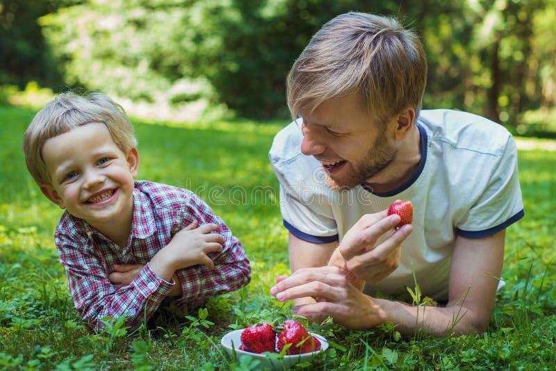 Padre feliz e hijo de la foto del verano junto que mienten en hierba verde imágenes de archivo libres de regalías