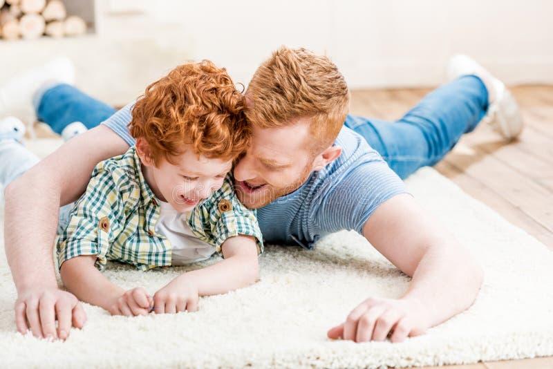 Padre feliz e hijo del pelirrojo que se divierten junto en la alfombra en casa imagen de archivo