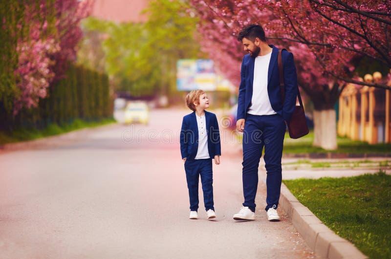 Padre feliz e hijo que caminan junto a lo largo de la calle floreciente de la primavera, trajes que llevan fotos de archivo