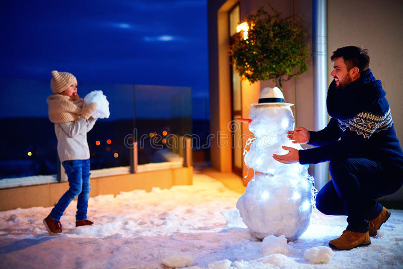 Padre feliz e hijo que hacen el muñeco de nieve en luz de la tarde foto de archivo libre de regalías