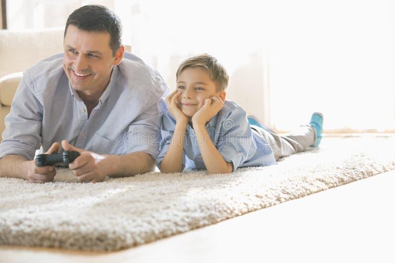 Padre feliz e hijo que juegan al videojuego en piso en casa imagenes de archivo