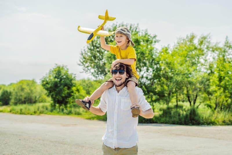 Padre feliz e hijo que juegan con el aeroplano del juguete contra viejo fondo de la pista El viajar con concepto de los niños imagen de archivo libre de regalías