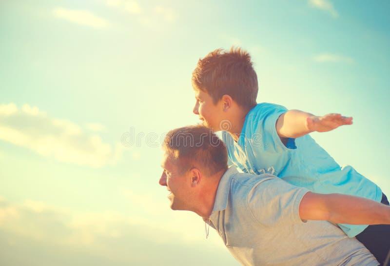 Padre feliz e hijo que se divierten sobre el cielo hermoso imagenes de archivo