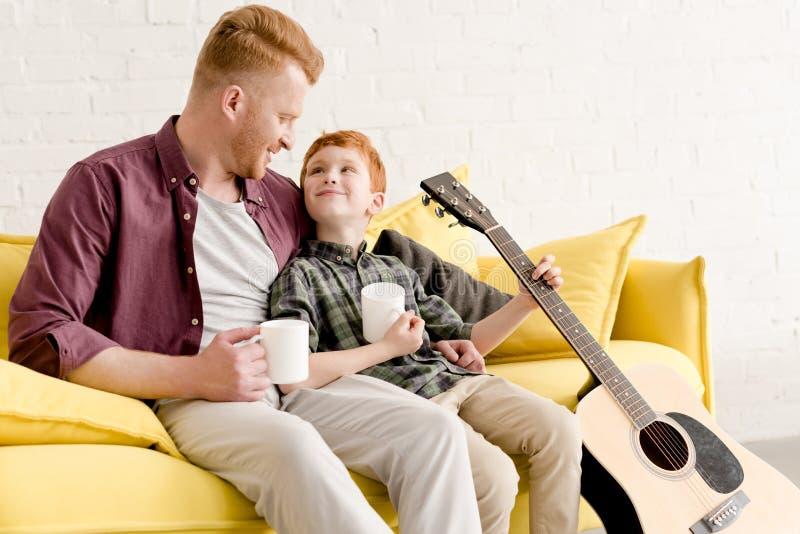 padre feliz e hijo que sostienen las tazas y la guitarra acústica mientras que se sienta en el sofá imagen de archivo libre de regalías