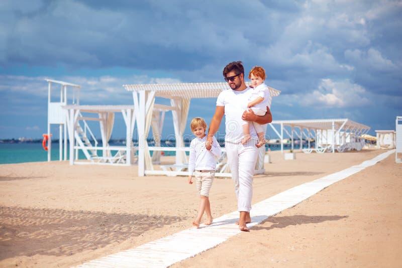 Padre feliz e hijos que caminan en la playa arenosa, vacaciones de verano en centro turístico tropical fotografía de archivo libre de regalías