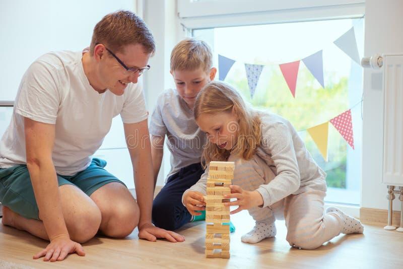 Padre feliz joven que juega con sus dos ni?os lindos con los bloques de madera foto de archivo libre de regalías