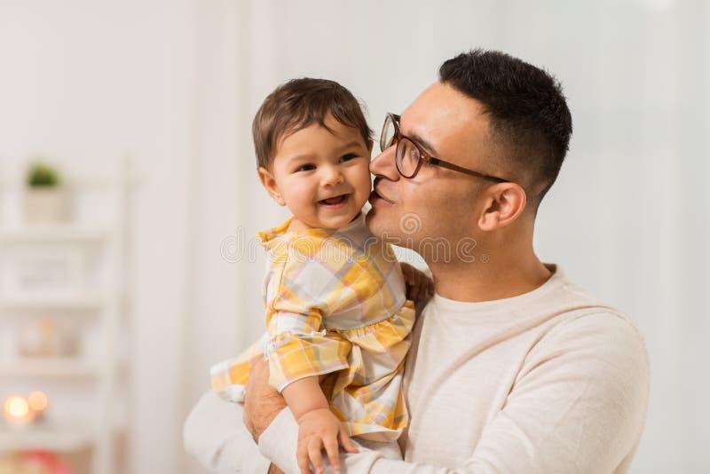 Padre feliz que besa a la pequeña hija del bebé en casa fotos de archivo