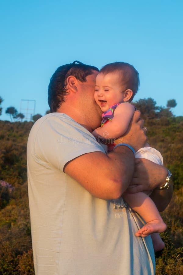 Padre feliz que besa a su pequeña hija foto de archivo libre de regalías