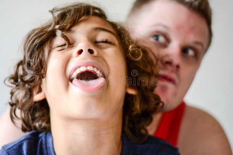 Padre feliz que juega con el muchacho en cocina imagenes de archivo