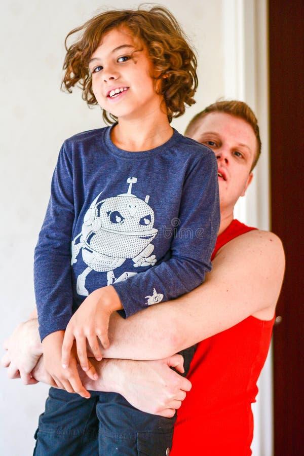 Padre feliz que juega con el muchacho en cocina imagen de archivo libre de regalías