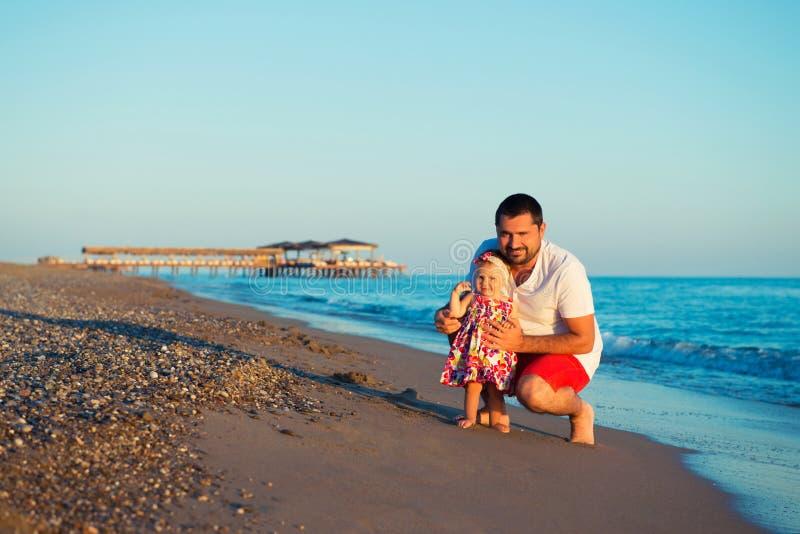 Padre feliz que juega con la pequeña hija linda en la playa imagen de archivo