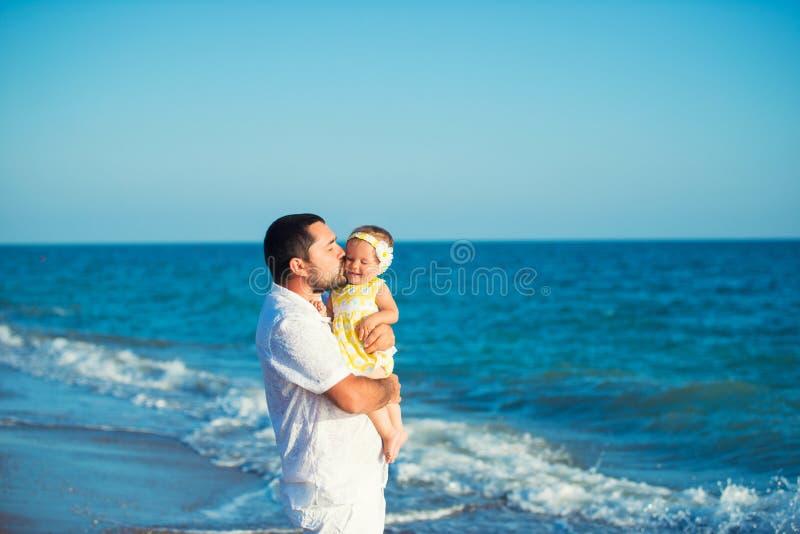 Padre feliz que juega con la pequeña hija linda en la playa Resto en Turquía imágenes de archivo libres de regalías