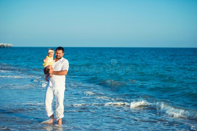 Padre feliz que juega con la pequeña hija linda en la playa Resto en Turquía fotos de archivo libres de regalías