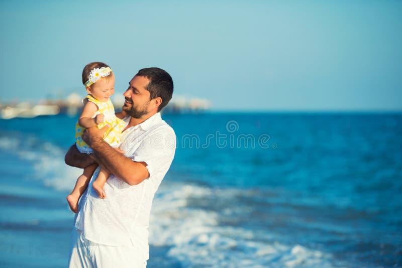 Padre feliz que juega con la pequeña hija linda en la playa Resto en Turquía foto de archivo libre de regalías