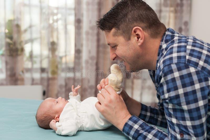 Padre feliz que juega con poco beb? en casa Familia, concepto de la paternidad fotos de archivo