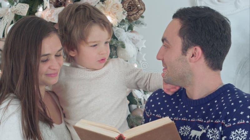 Padre feliz que lee sobre la barba de Papá Noel, mientras que madre que celebra a su hijo juguetón delante del árbol de navidad imagenes de archivo