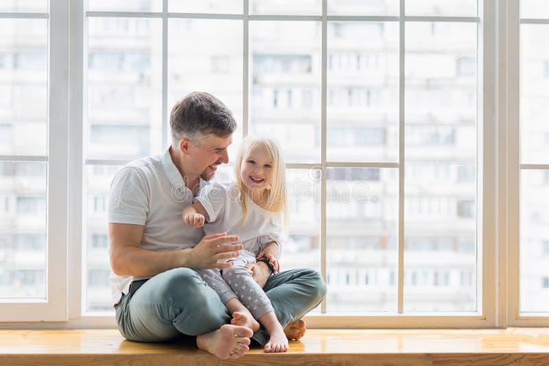 Padre feliz sentado en la ventana mientras da un abrazo a su hija de 3 años foto de archivo