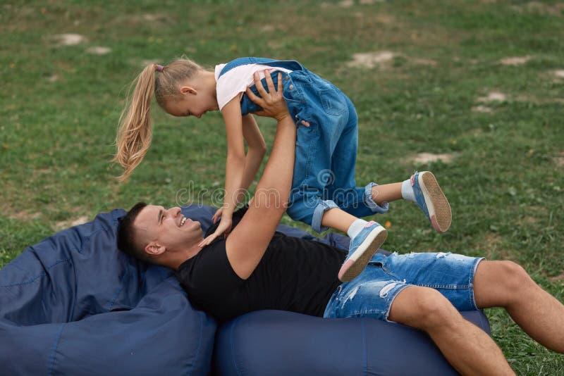 Padre feliz y doughter que se divierten y que juegan al aire libre, sentándose en la silla frameless, pasando el tiempo junto en  foto de archivo libre de regalías