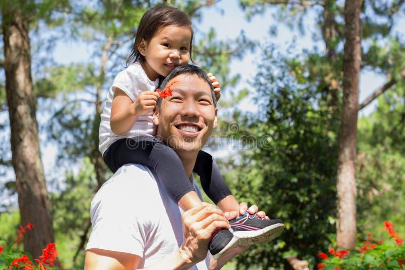Padre feliz y niño que ríen y que juegan junto, hija que cuida en el suyo detrás en un Forest Park al aire libre foto de archivo