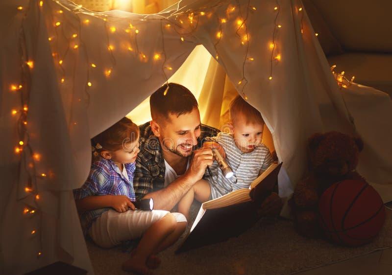 Padre feliz y niños de la familia que leen un libro en tienda en el hom imagen de archivo libre de regalías