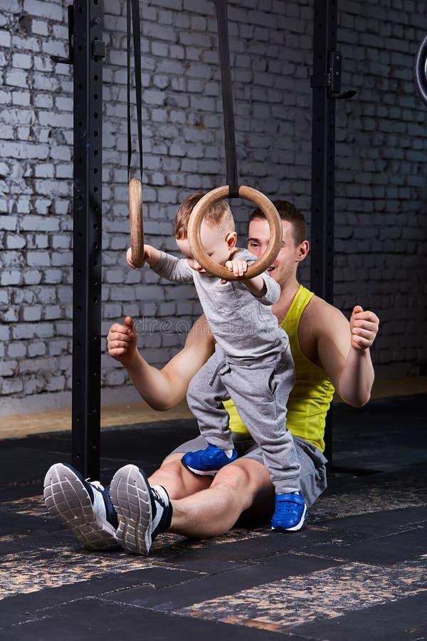 Padre feliz y pequeño hijo lindo que ejercitan con los anillos contra la pared de ladrillo foto de archivo libre de regalías