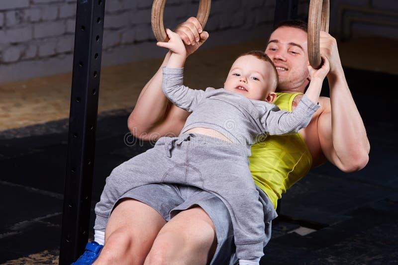 Padre feliz y pequeño hijo lindo que ejercitan con los anillos y la sonrisa imagen de archivo