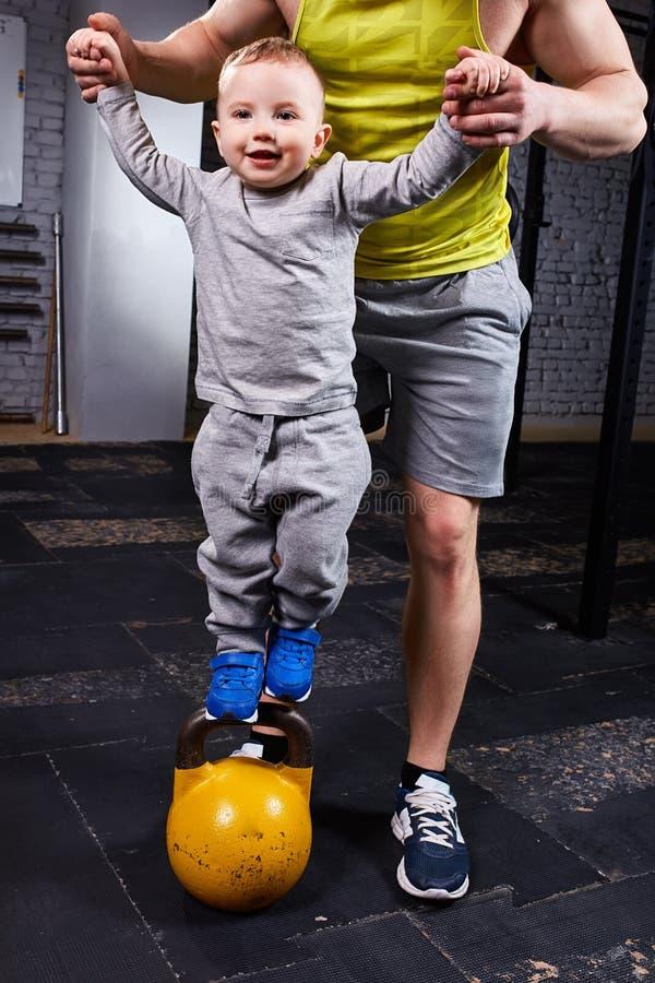 Padre feliz y pequeño hijo lindo que ejercitan con pesas de gimnasia y que sonríen mientras que contra la pared de ladrillo imagen de archivo libre de regalías