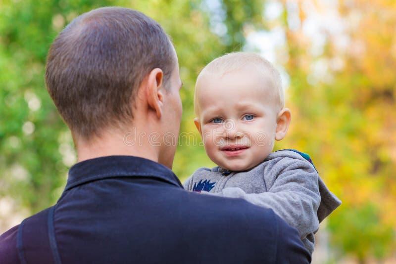Padre feliz y su hijo al aire libre Niño que abraza al papá fotos de archivo